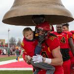 A YOUNG BULLDOG SHARES IN THE TRADITIONAL RINGING OF THE VICTORY BELL.