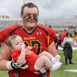 A BULLDOG LINEMAN POSES WITH A YOUNG FAN.