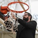 HEAD BASKETBALL COACH ANDY BRONKEMA CELEBRATES BY CUTTING DOWN THE NETS.