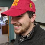 ALUMNI RELATIONS COORDINATOR KEVIN BUNCE MODELS THE CO-BRANDED HAT GIVEN OUT AT THE EVENT.