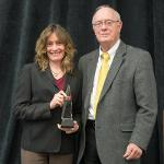 TRACY BUSCH RECEIVES THE DISTINGUISHED TEACHER AWARD FORM PROVOST PAUL BLAKE.