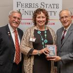 PRESIDENT DAVID EISLER AND ALUMNI ASSOCIATION PRESIDENT ANDY YOUNG (L) PRESENTED PAMELA CURTIS ('86) WITH THE DISTINGUISHED ALUMNI AWARD.