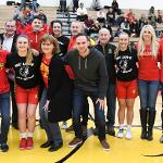 SENIORS ON THE WOMEN'S BASKETBALL TEAM POSE WITH THEIR HEAD COACH AND FAMILIES.