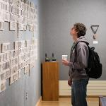 "A STUDENT BROWSES THE ""GOOD JUJU"" EXHIBIT AT THE FSU FINE ART GALLERY."
