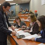 PETER BRADLEY, DIRECTOR OF THE HONORS PROGRAM, CONFERS WITH THE JUDGES.
