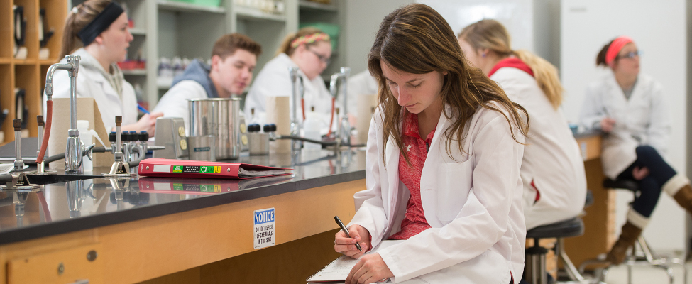 Student in a lab coat writing down information